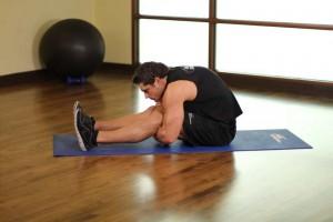 Растяжка мышц обхватывая бедра в положении сидя, позиция 1